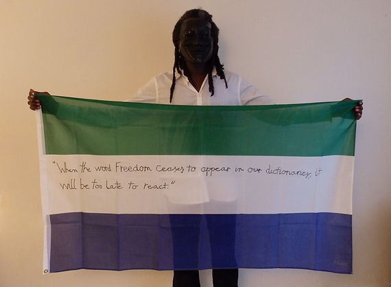 Art warning the World, Sierra Leone - Monka and his flag with the Klaus Guingand sentence in English / Flag: 35,5 x 59 in/ Sentence black pen / Signed