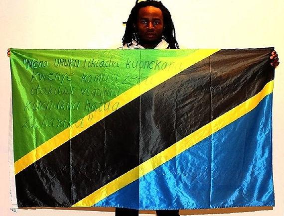 Art warning the World, Tanzania - Mmbando Kennedy and his flag with the Klaus Guingand sentence in Kiswahili.