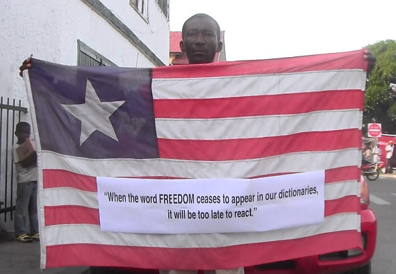 Art warning the World - Liberia -  Leslie Lumeh and his flag with the Klaus Guingand sentence in English / Flag: 35,5 x 59 in./ Sentence print on paper / Signed