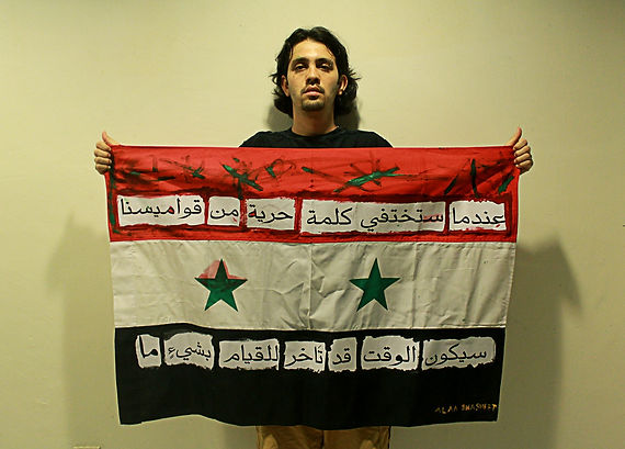 Art warning the World, Syria - Alaa Shasheet and his flag with the Klaus Guingand sentence in Arabic / White & black paint / signed