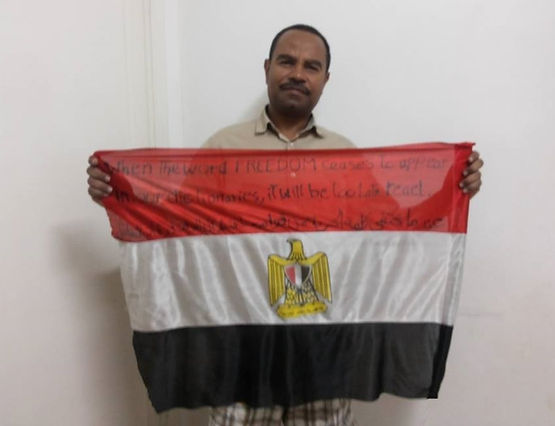 Art warning the world, Egypt -Omar Abdelzaher and his flag with the Klaus Guingand sentence in Arabic and English / Black paint / Signed