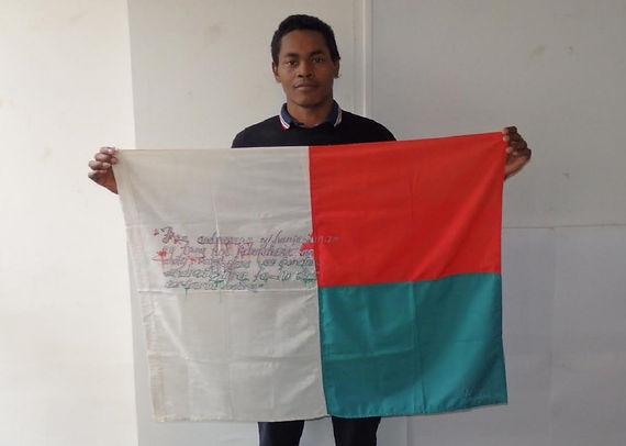 Art warning the World, Madagascar - ​ Tagman Airjp and his flag with the Klaus Guingand sentence in Malagasy. Flag: 35,5 x 59 in. / Sentence black & red pen / Signed