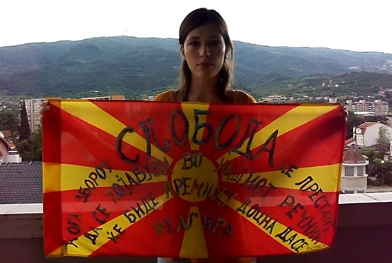 Art warning the World, Macedonia - Aleksandra and her flag with the Klaus Guingand sentence in Macedonian / Flag: 17,71 x 39,37 in. / Sentence brown & gold paint / Signed