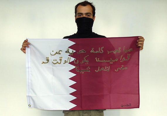 Art warning the World, Qatar - Alassane and his flag with the Klaus Guingand sentence in Arabic / Flag: 23 x 35,4 in./Sentence black & gold marker pen / Signed