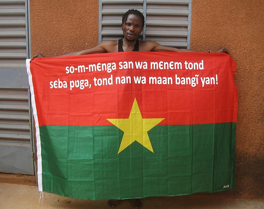 Art warning the World, Burkina Faso - Boureima Nabaloum and his flag with the Klaus Guingand sentence in Moore.