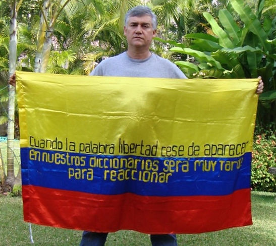 Art warning the world, Colombia - Jorge Restrepo and his flag: 35:5 x 59 inches / Sentence in Spanish / Black & yellow paint / Signed