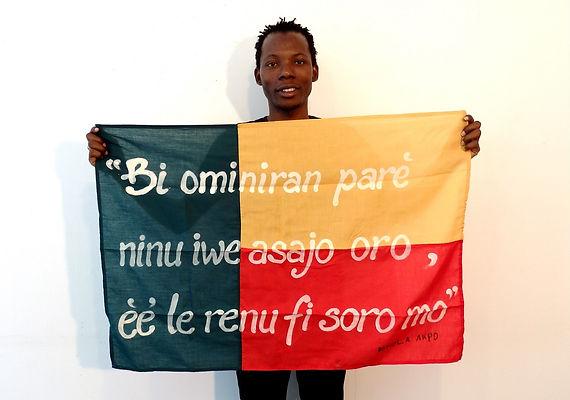 Art warning the World / Benin - Ishola Akpo and his flag: with the Klaus Guingand sentencein Yoruba.