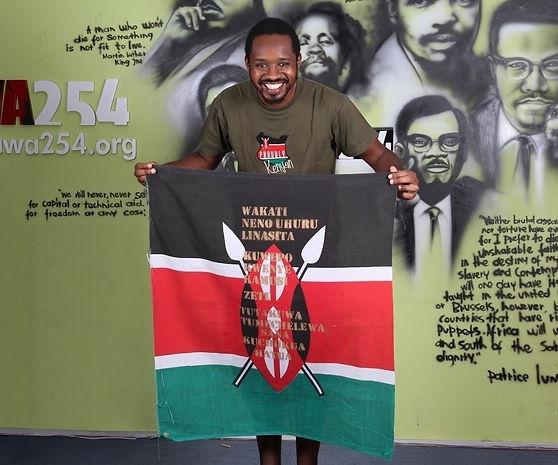 Art warning the World, Kenya - Boniface Mwangi and his flag with the Klaus Guingand sentence in Swahili / Digital printing / Signed