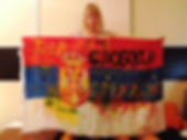 Art warning the World, Serbia - Irena ZFT and her flag with the Klaus Guingand sentence in Serbian / Flag 35,5 x 59 in./ Sentence yellow, black & red paint / Signed