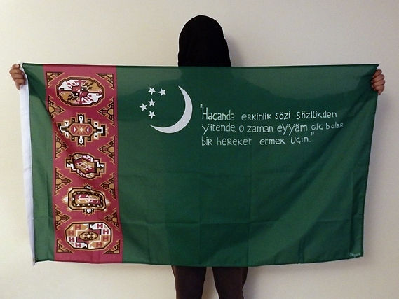 ​Art warning the World,Turkmenistan - Begench and his flag with the Klaus Guingand sentence in Turcoman.