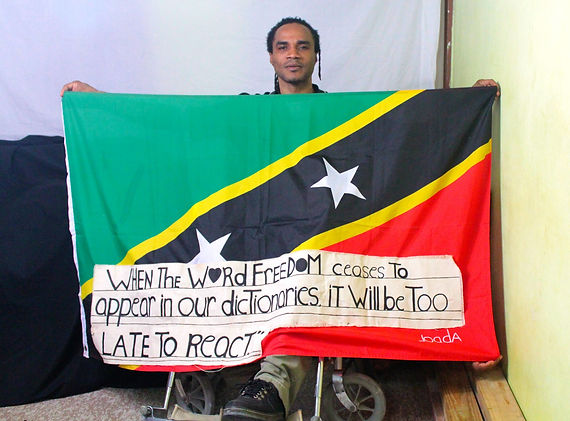 Art warning the World, St. Kitts and Nevis - Junior Versailles and his flag with the Klaus Guingand sentence in English / Flag: 35,5 x 59 in. / Sentence sticky paper / Signed
