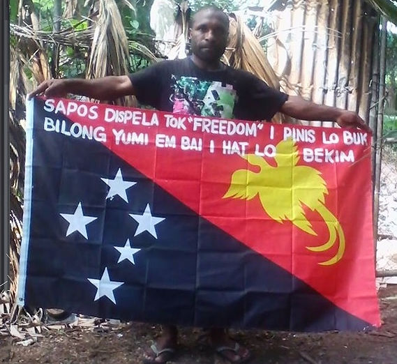 Art warning the World, Papua New Guinea - Alberto Joseph and his flag with the Klaus Guingand sentence in Tok pisin / Flag: 35,5 x 59 in. / Sentence white paint / Signed