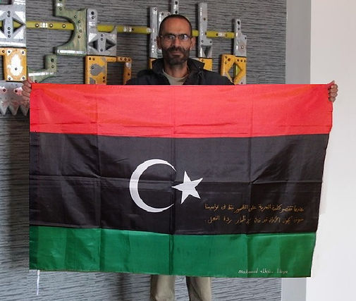 Art warning the World, Libya - Mahmoud G. Alhasi and his flag with the Klaus Guingand sentence in Arabic / Flag: 35,5 x 59 in. / Sentence gold paint / Signed