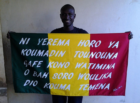 Art warning the World, Mali -  Ahmadou Landouré and his flag with the Klaus Guingand sentence in Bambara / Flag: 23,62 x 74,24 in./ Sentence white paint / Signed.