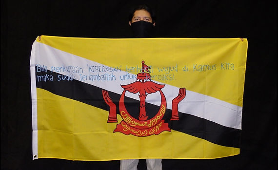 Art warning the World / Brunei - Cay Kan and his flag with Klaus Guingand sentence in Malay-Brunei.