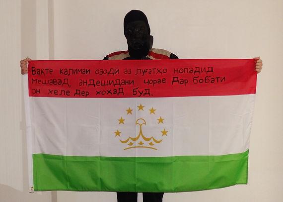 Art warning the World, Tajikistan - Sodromak and his flag with the Klaus Guingand sentence in Tajik.