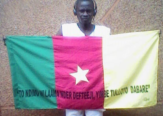 Art warning the world / Cameroon - Walter Teguelet and his flag with the Klaus Guingand sentence in Fulfulde.