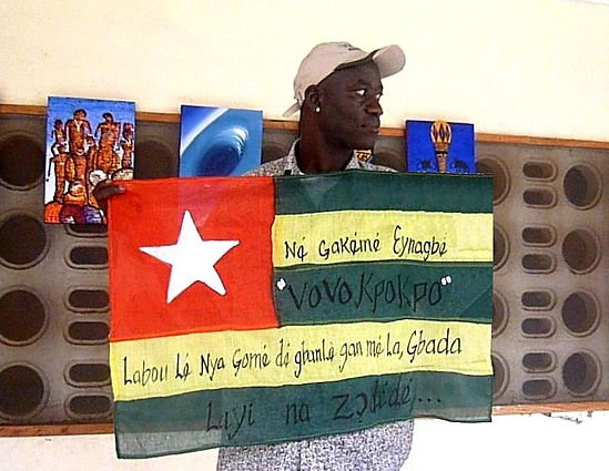 Art warning the World, Togo - Art Angelo and his flag with the Klaus Guingand sentence in Ewe.