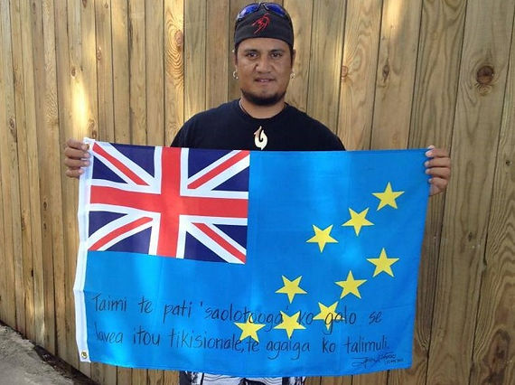 Art warning the World,Tuvalu - John Alefaio and his flag with the Klaus Guingand sentence in Tuvaluan.