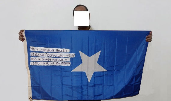 Art warning the World, Somalia - Kasim and his flag with the Klaus Guingand sentence in Somali / Flag: 35,5 x 59 in. / Sentence white paint & black marker/ Signed