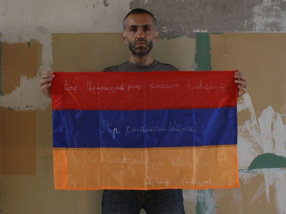 Art warning the World - Armenia - Aleksey Manukyan and his flag with the Klaus Guingand sentence in Armenian / White marker pen / Signed