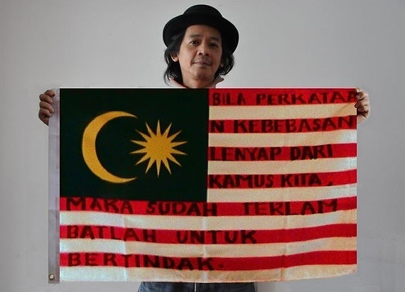 Art warning the World, Malaysia -  Amir Zainorin and his flag with the Klaus Guingand sentence in Malaysian / Flag: 23 x 35,4 in. / Sentence black marker pen / Signed