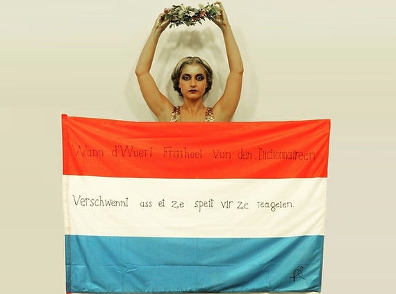 Art warning the World / Luxembourg - Deborah De Robertis) and her flag with the Klaus Guingand sentence in Luxembourgish
