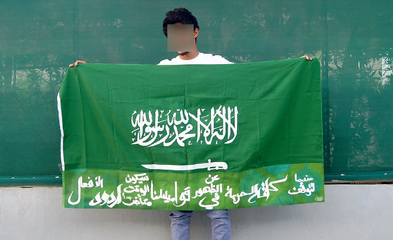 Art warning the World, Saudi Arabia - Noos and his flag with the Klaus Guingand sentence in Arabic / Flag: 45,2 x 66 in. / Sentence white paint / Signed