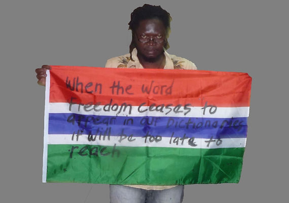 Art warning the World, Gambia - Etu Ndow and his flag with the Klaus Guingand sentence in English / Black & gold marker / Signed