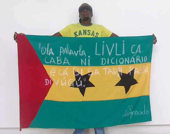 Art warning the World, Säo Tomé and Principe - Olavo Amado and his flag with the Klaus Guingand sentence in Santome / Flag: 35,5 x 59 in. / Sentence white chalk / Signed