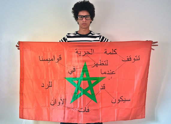 Art warning the World, Morocco - Hamza Robati and his flag with the Klaus Guingand sentence in Arabic / Flag: 35,5 x 59 in. / Sentence black paint / Signed