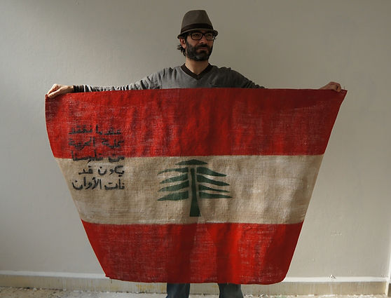 Art warning the World, Lebanon - Semaan Khawam and his flag with the Klaus Guingand sentence in Arabic / Black paint / Signed