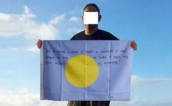 Art warning the World, Palau - Osei and his flag with the Klaus Guingand sentence in Palauan / Flag: 23 x 35,4 in. / Sentence black marker / Signed