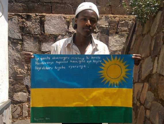 Art warning the World, Rwanda - Niyonnkuru Bruce and his flag with the Klaus Guingand sentence in Kinyarwanda / Flag: 18,89 x 23,62 in. / Sentence white marker pen / Signed