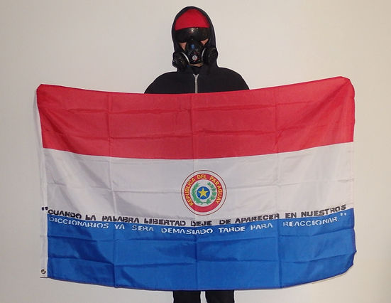 Art warning the World, Paraguay - Vandal Calle and his flag with the Klaus Guingand sentence in Spanish / Flag: 35,5 x 59 in. / Sentence white & black paint / Signed