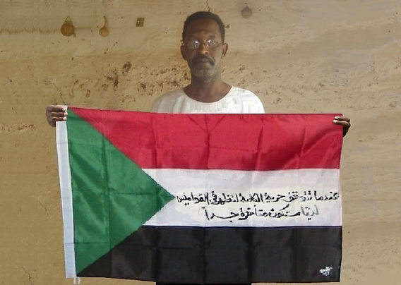 Art warning the World, Sudan - Amar Younis and his flag with the Klaus Guingand sentence in Arabic.