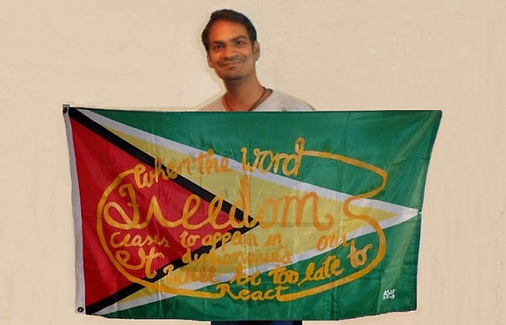 Art warning the World, Guyana - Asif Hakh and his flag with the Klaus Guingand sentence in English / Yellow paint / Signed