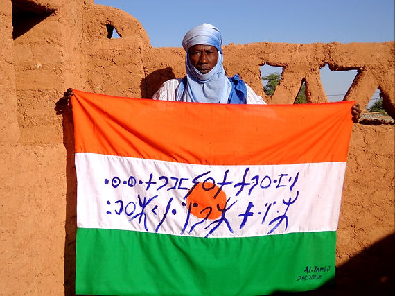 Art warning the World,Niger /Almoustapha Tambo and his flag with the Klaus Guingand sentence in Tifinagh / Flag: 35,5 x 59 in. / Sentence blue paint / Signed