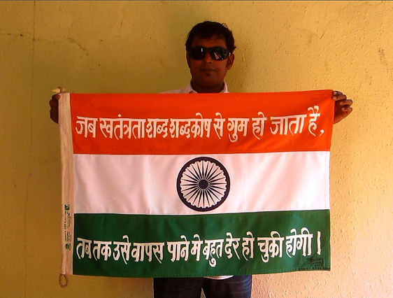 Art warning the world, India - Uday Shanbhag and his flag: 23 x 35,4 inches/ Sentence in Hindi / White paint / Signed