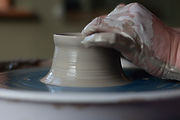 Studio  LP Ceamics pulling a wall on  pot on the potters wheel.