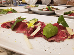 Cured meats and greens carefully arranged into an appetizer by Personal Chef Mike