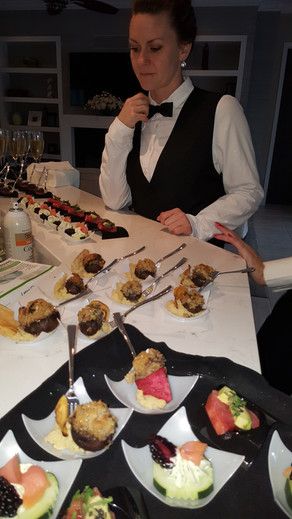 A server prepares to deliver a collection of Hors D'oeuvres during greeting time at a cocktail party.