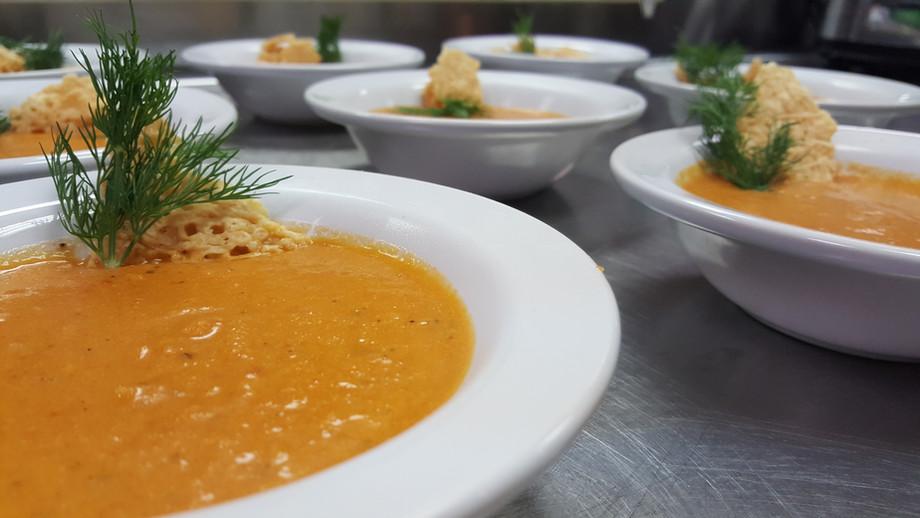 An orange soup with a green garnish.