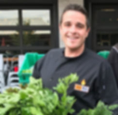 Chef Mike holding organic produce at a local Sarasota Farmer's Market