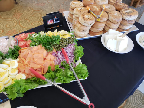 Bagels and salad trays laid out on a buffet table for a meeting.