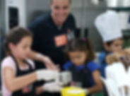 Chef Mike smiles as he helps young kid chef measure flour.