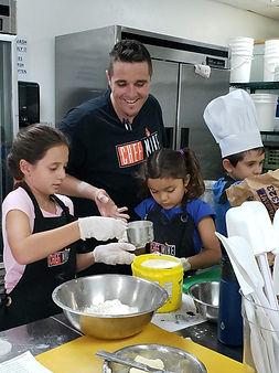 Chef Mike teaching young kids how to bake.