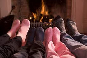 People warming their feet by a fireplace