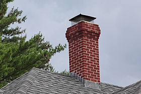 A chimney with a protective cap and screen on it