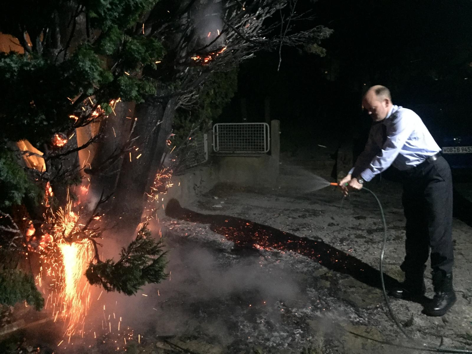 Mutig gegen die Feuersbrunst mit dem Gartenschlauch